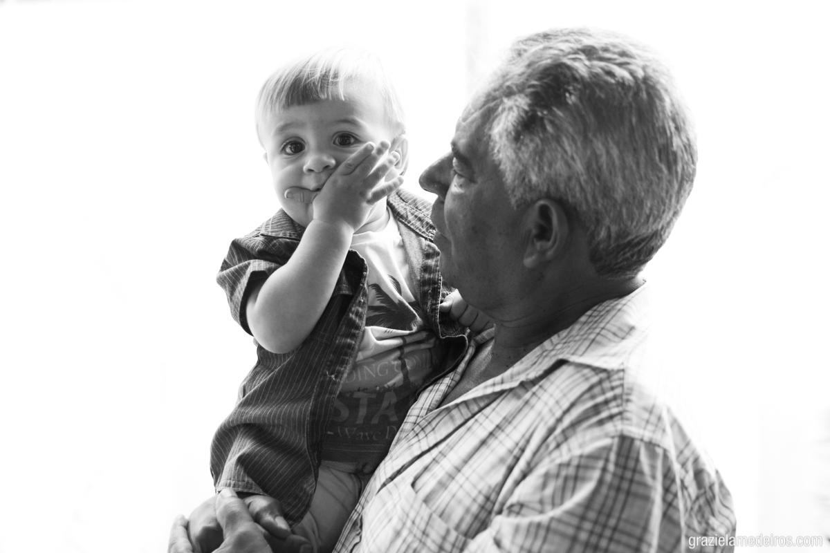 fotografia de criança com mandando beijo no colo do avô em sua festa de aniversário de um ano na cidade de Itamogi MG