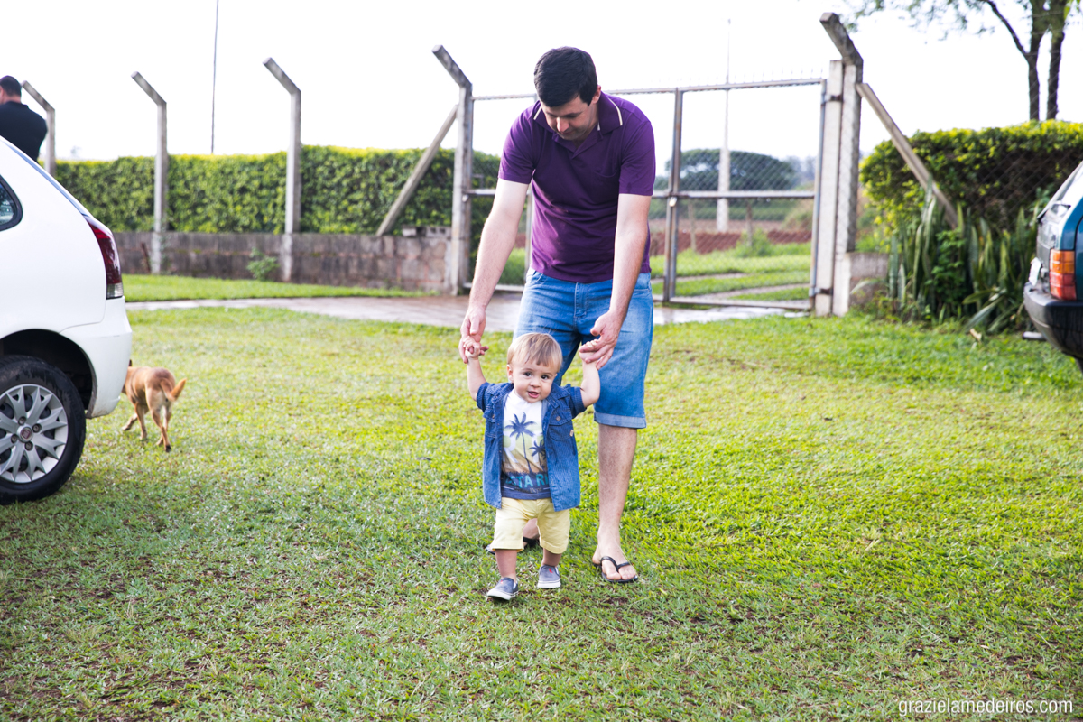 fotografia de criança dando seus primeiros passos na grama segurando as mãos do pai na sua festa de aniversario em casa na cidade de Itamogi MG