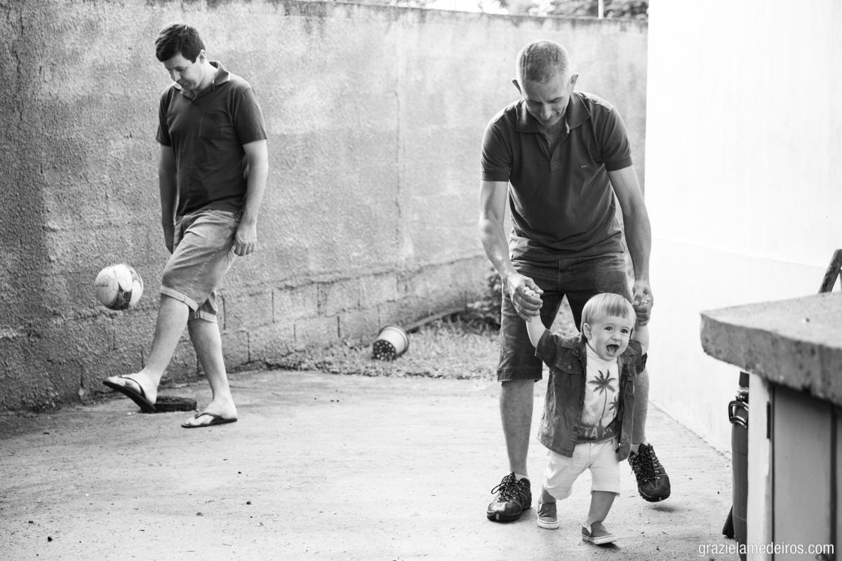 fotografia de criança dando os primeiros passos segurando as mãos de seu padrinho enquanto seu pai joga bola em sua festa de um ano em Itamogi MG