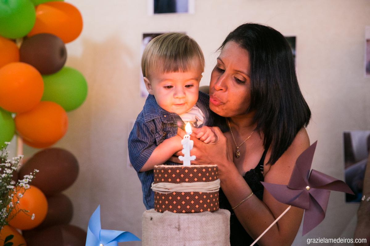 fotografia da criança assoprando a velinha de aniversario do seu primeiro ano depois de cantar parabens em Itamogi MG