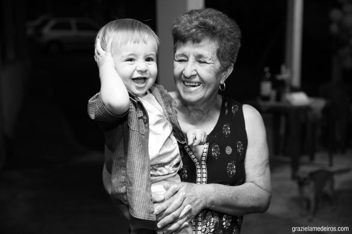 fotografia da criança sorrindo no colo da avó em sua festa de aniversario em Itamogi Mg