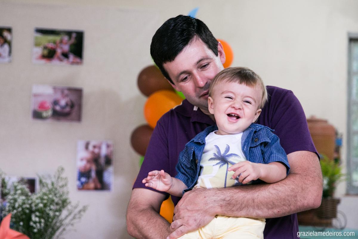 fotografia da criança sorrindo no colo do pai na sua festa de aniversario feita em casa no seu primeiro aniversario