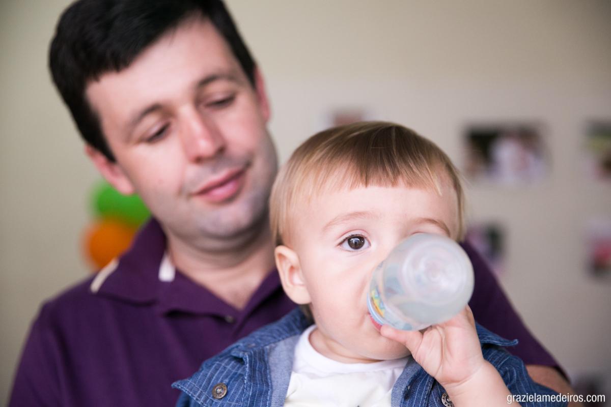 fotografia de criança tomando agua na mamadeira, no colo do pai, em casa, no seu aniversario de um ano em Itamogi-MG