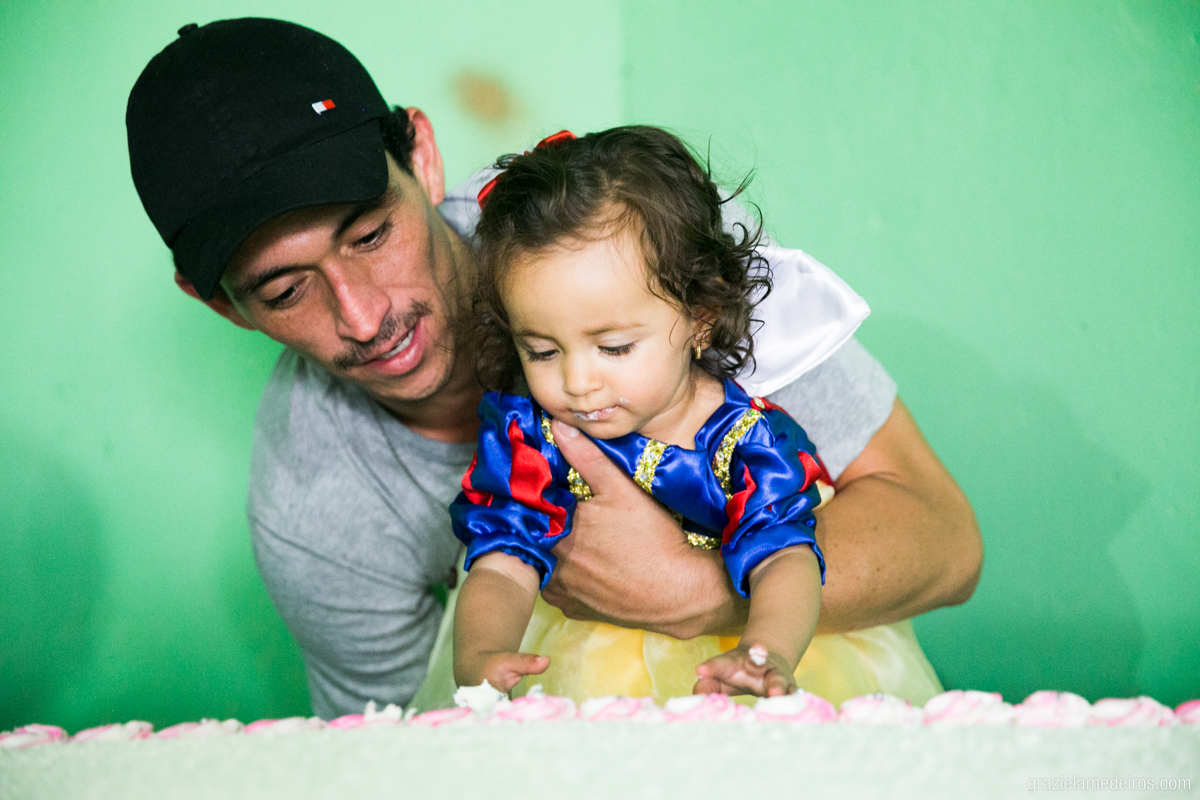menina vestida de branca de neve comendo bolo com o pai no seu anversario de um ano