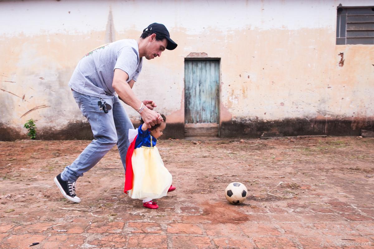 menina com fantasia de branca de neve jogando bola com o pai no seu aniversario de um ano