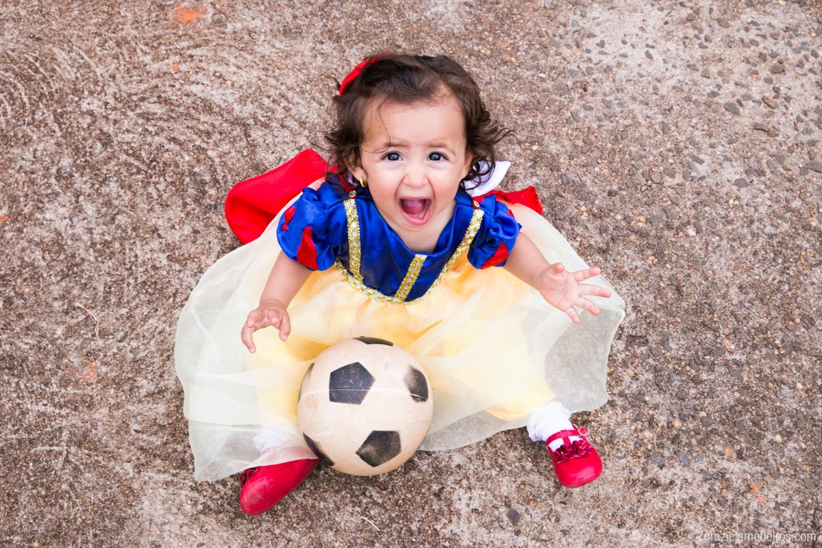 menina sentada no chao vestida de branca de neve brincando de bola na sua festa de aniversaio de um ano