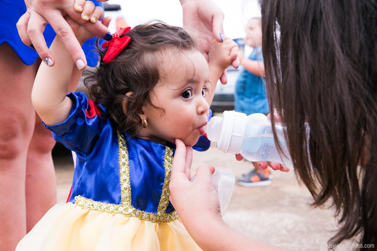 criança vestida de branca de neve tomando agua na mamadeira na sua festa de aniversario de um ano