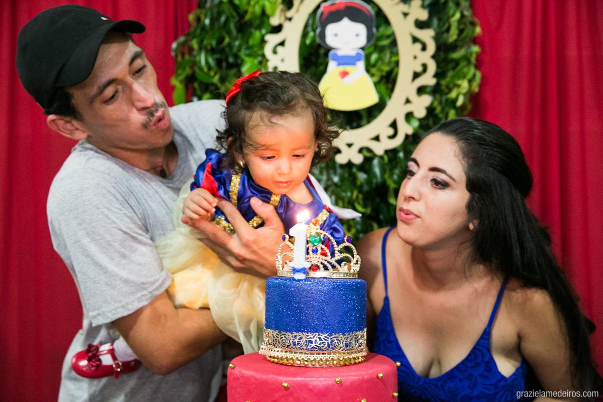 criança vestida de branca de neve cantando parabens na mesa do bolo da sua festa de aniversario de um ano
