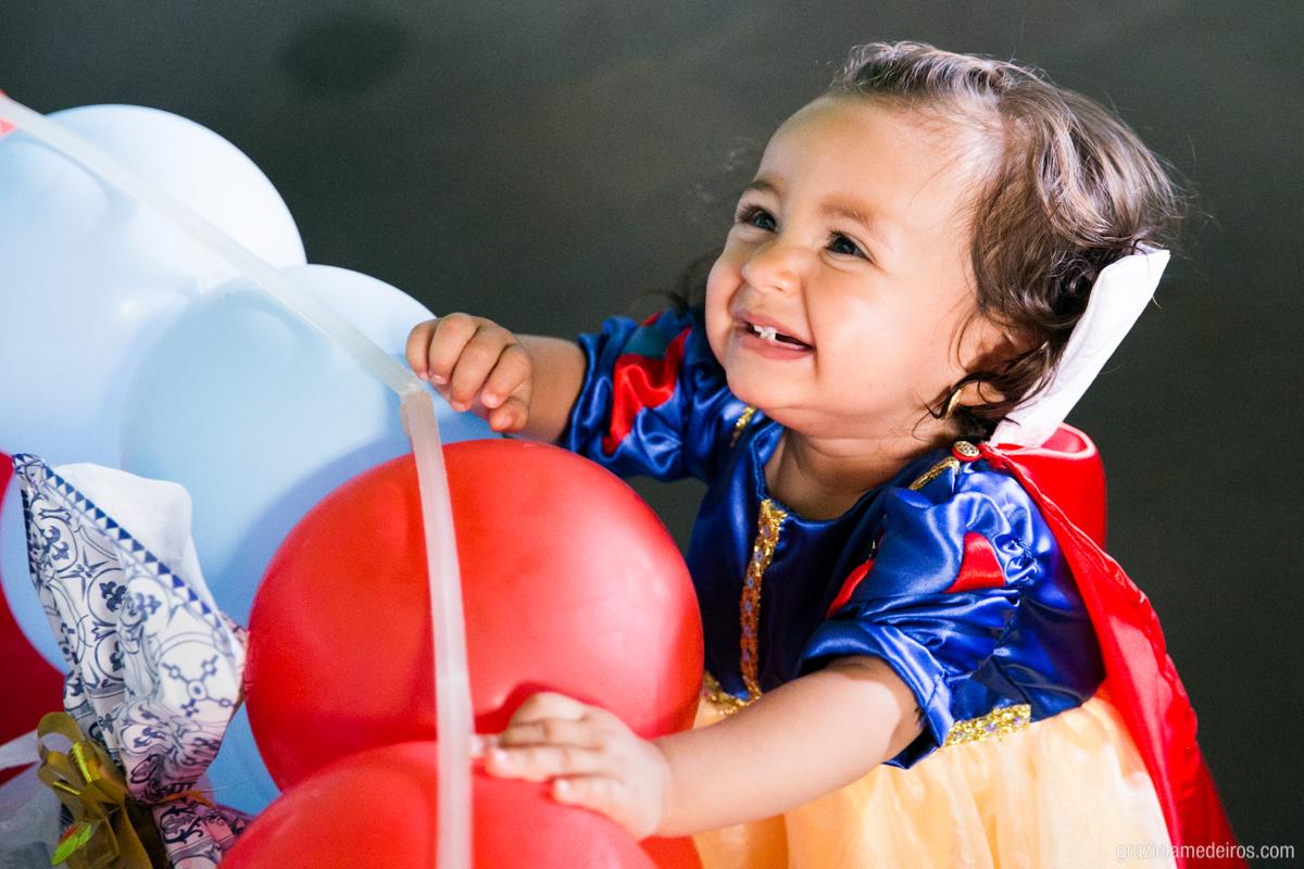 menina vestida com a fantasia da branca de neve em sua festa de aniversario de um ano brincando com baloes