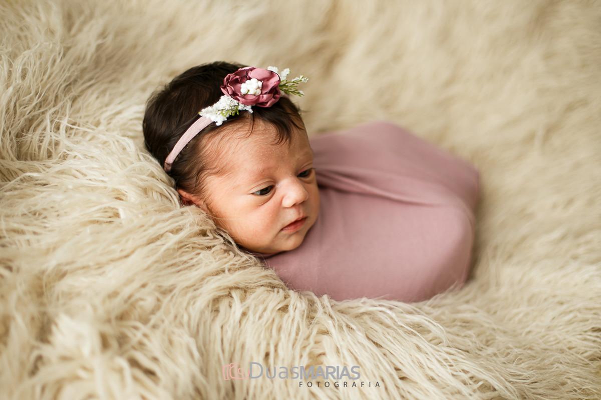 Bebê recém nascida enrolada no wrap, deitada em prop peludo