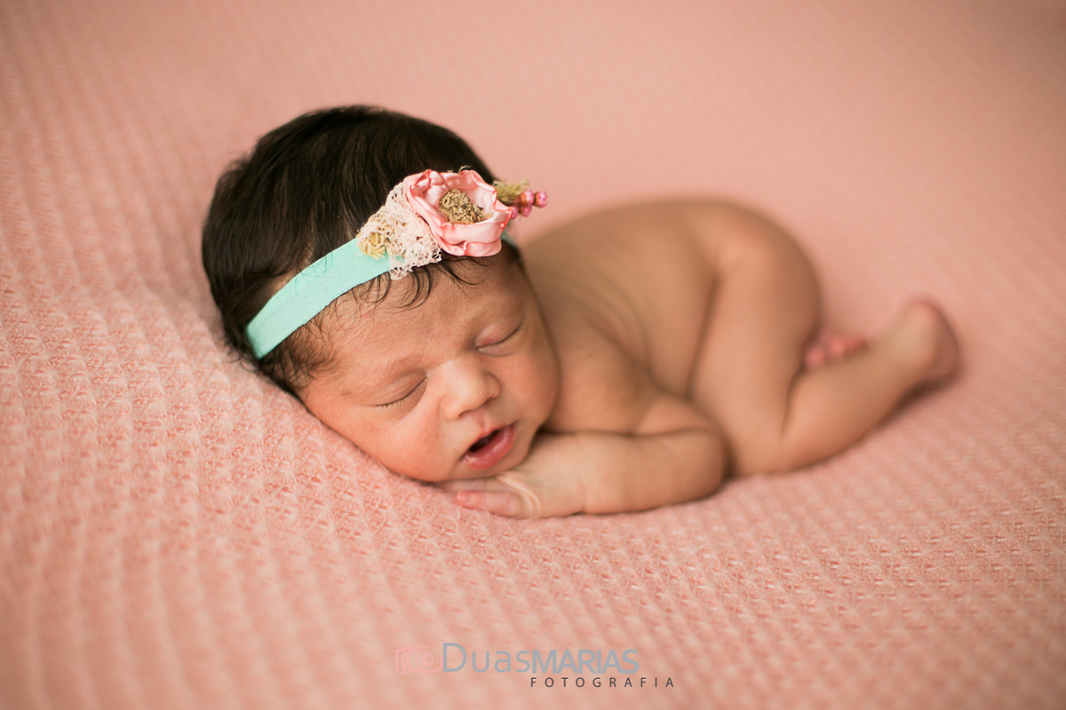 Bebê recém nascida peladinha deitada encolhida na mata rosa