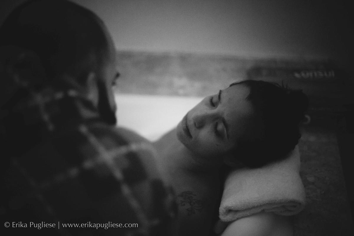 Pai observa a mãe na banheira durante o trabalho de parto fotografado por Erika Pugliese