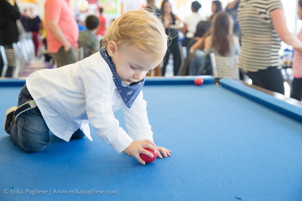 Criança brinca em cima da mesa de bilhar enquanto é fotografado