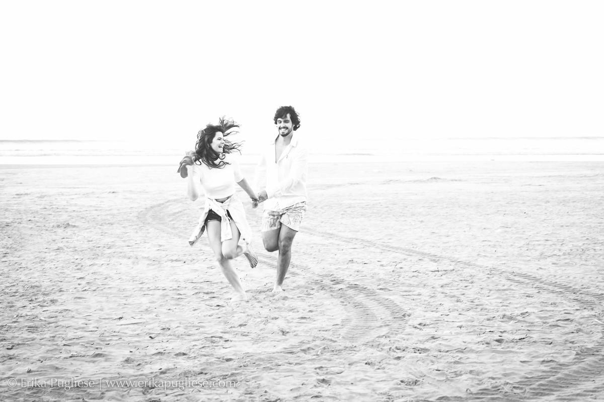 Divertidos o casal corre na praia para o ensaio de Erika Pugliese