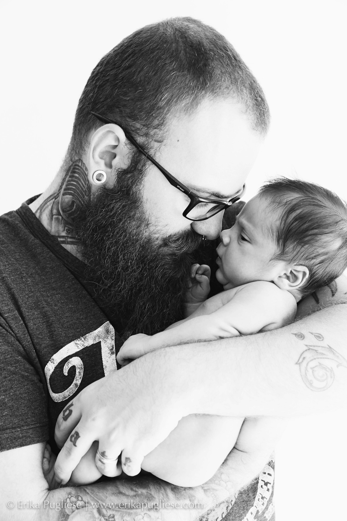 Pai estiloso segura seu bebê na sessão newborn