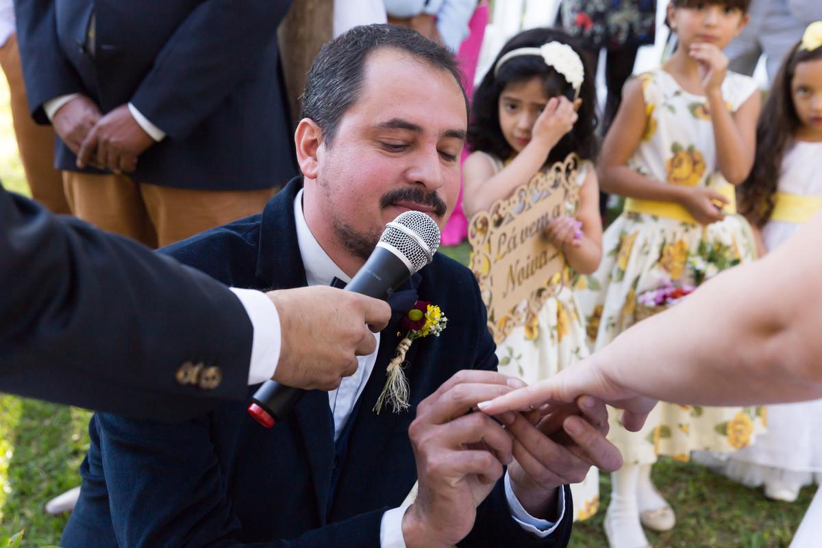 Noivo se ajoelha diante da noiva no altar durante o casamento para colocar a aliaça