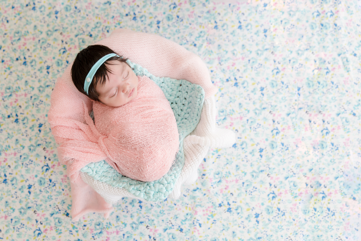 bebê em fundo floral no ensaio newborn