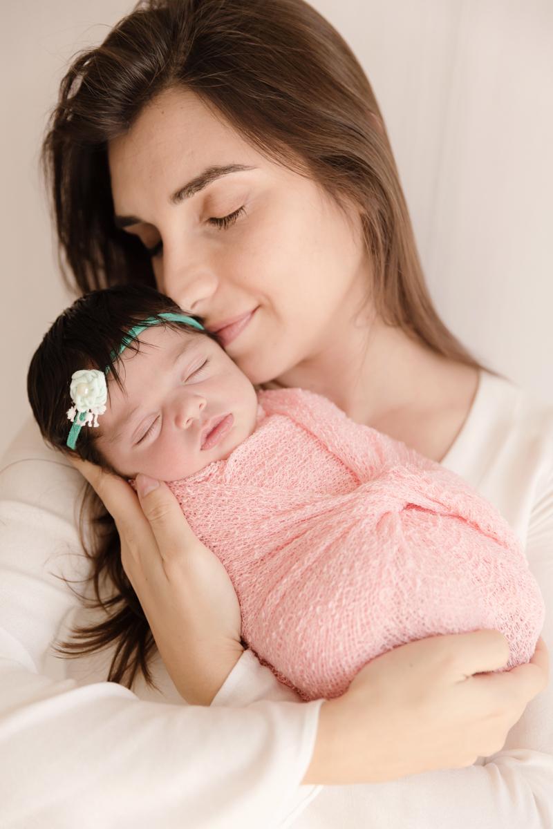 mamãe segura bebê em ensaio de recém nascido