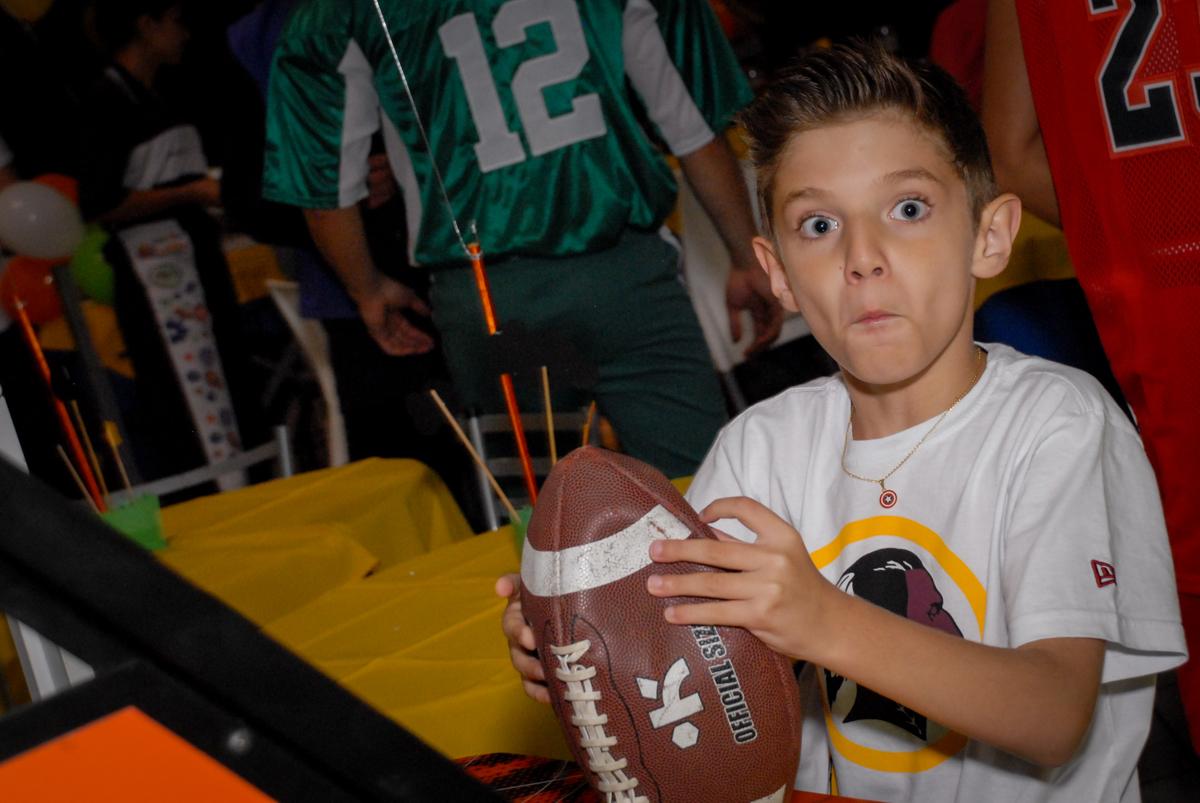 O aniversariante joga futebol americano no Buffet Fábrica da Alegria, Osasco, Sao Paulo, tema da festa esportes americanos, aniversariante Matheus 8 anos