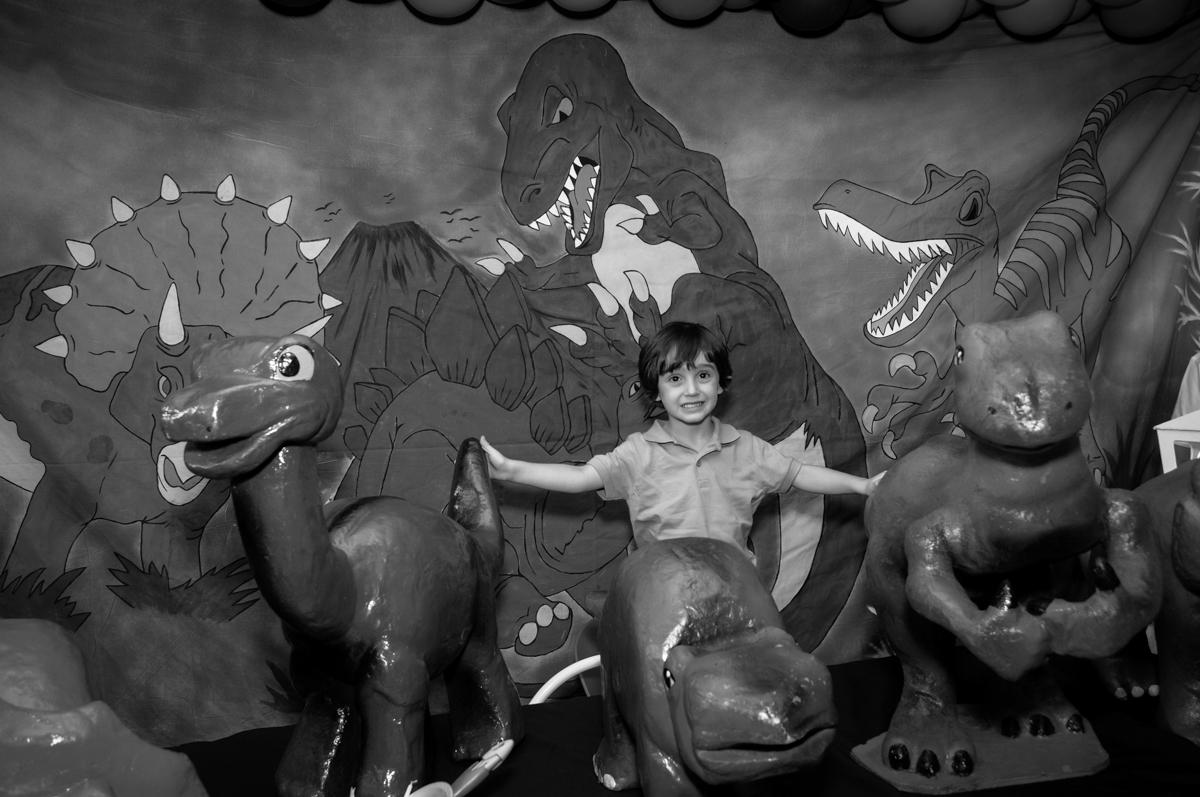 Alegria do aniversariante em sua festa no Buffet Planeta 2, Butantã, SP, festa infantil fotografia infantil, aniversário de Fabrício 4 anos tema da mesa dinossauros