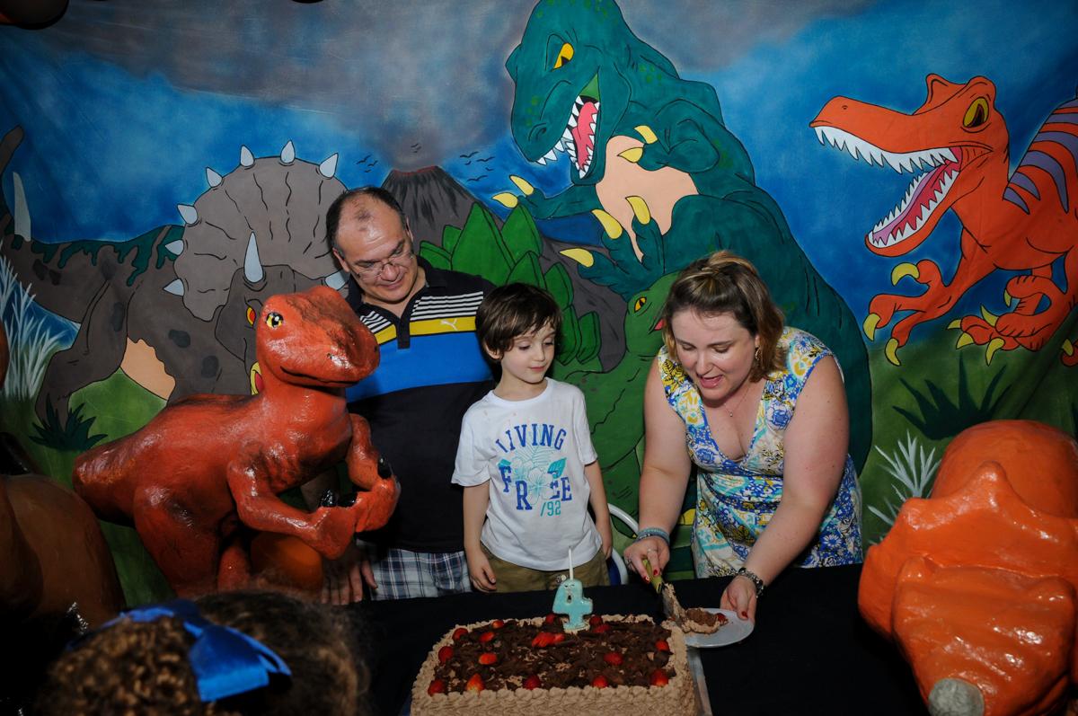 cortando o bolo, quem vai ganhar o primeiro pedaço de bolo? no Buffet Planeta 2, Butantã, SP, festa infantil fotografia infantil, aniversário de Fabrício 4 anos tema da mesa dinossauros