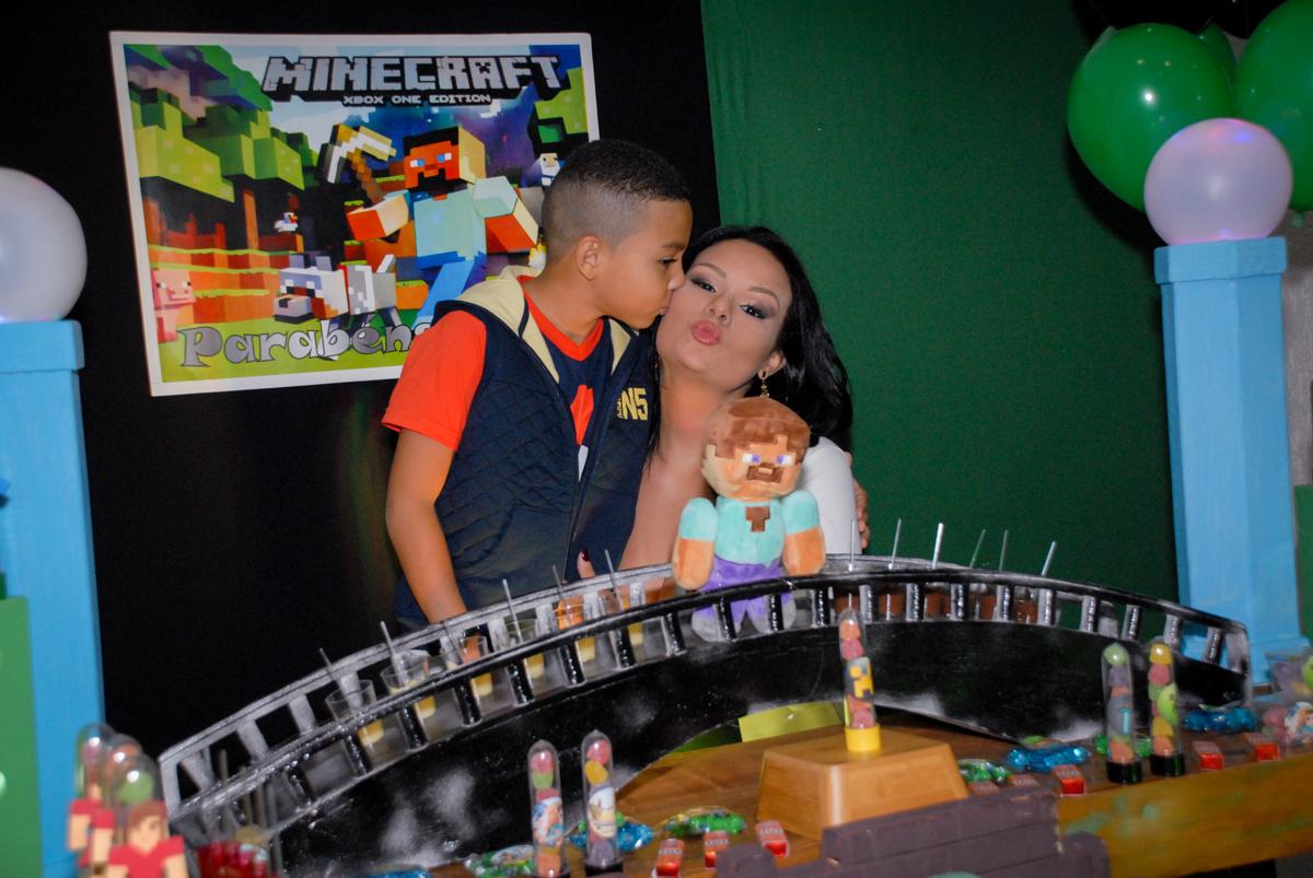 beijo carinhoso da mamãe na Aniversário infantil, festa de Guilherme 7 anos tema da mesa minicraft, no Buffet Fábrica da Alegria, Morumbi,SP