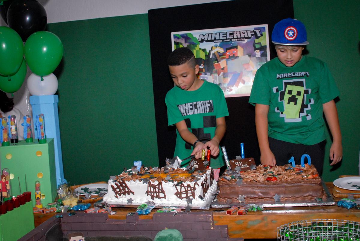 cortando o primeiro pedaço de bolo na Aniversário infantil, festa de Guilherme 7 anos tema da mesa minicraft, no Buffet Fábrica da Alegria, Morumbi,SP