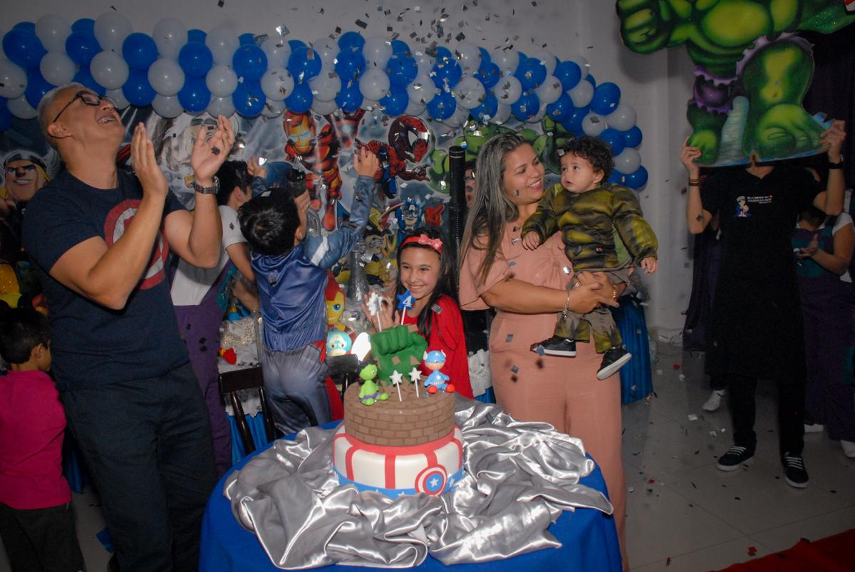 cortando o primeiro pedaço de bolo no Buffet Galeria da Arte, Vila Maria, São Paulo, aniversário de Lorenzo 4 e Lucca 1 aninho tema da festa super herois