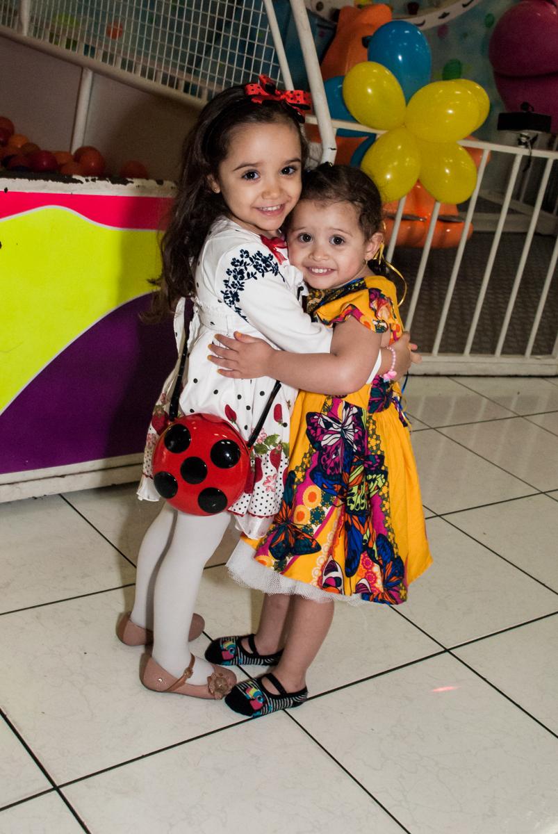 recebendo a amiga com abraço no Buffet Lacorte, Tatuapé, São Paulo aniversário de Luiza 3 anos, tema da festa A Bela e a Fera