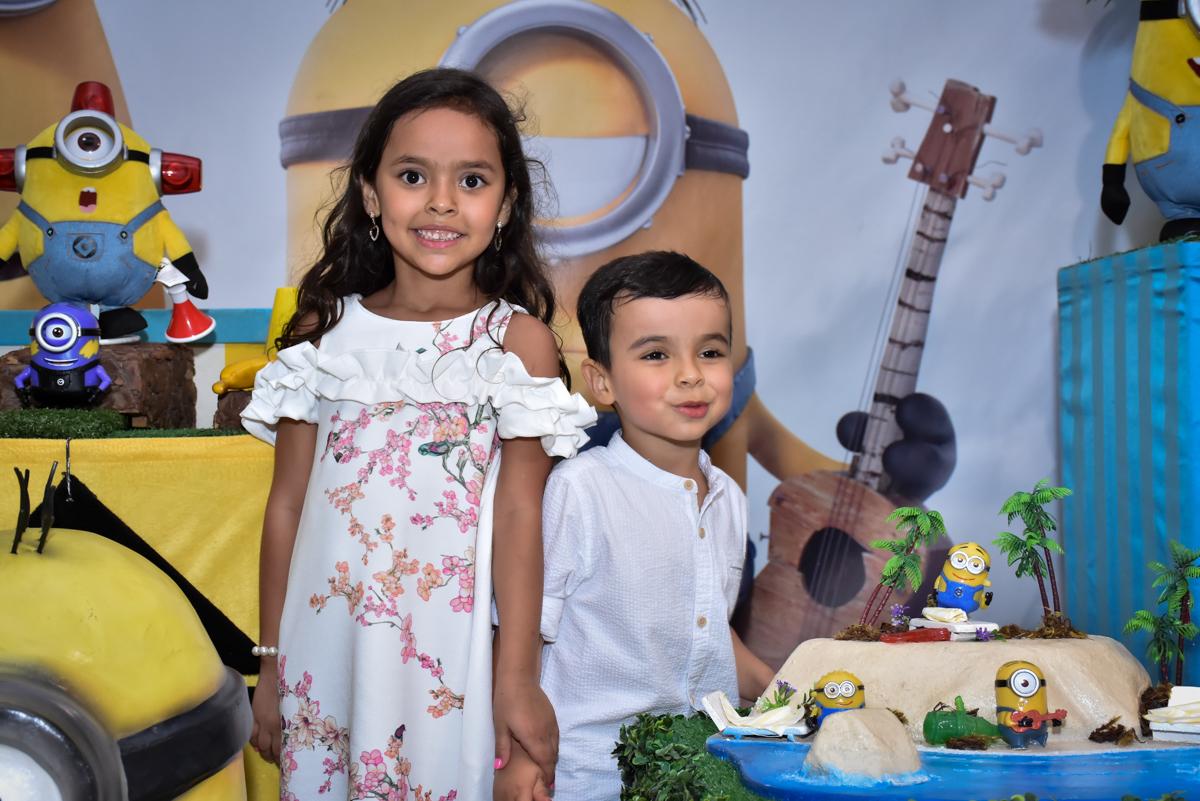 foto dos irmãos na mesa temática no Buffet Fábrica da Alegria, Osasco, São Paulo, tema da festa, meu malvado favorito