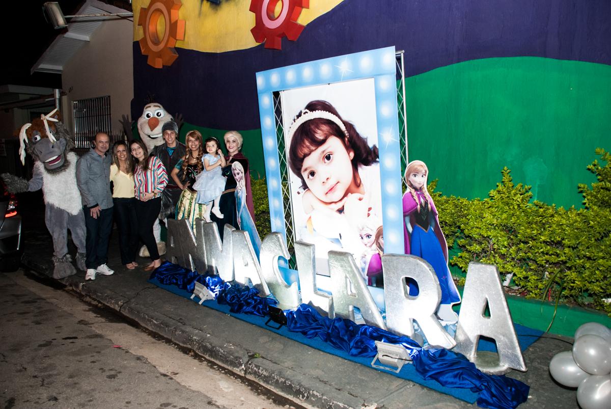 fotografia da família na fachada de cinema no Buffet Fábrica da Alegria, Osasco, São Paulo, aniversário de anna clara, 3 anos, tema da festa Frozen