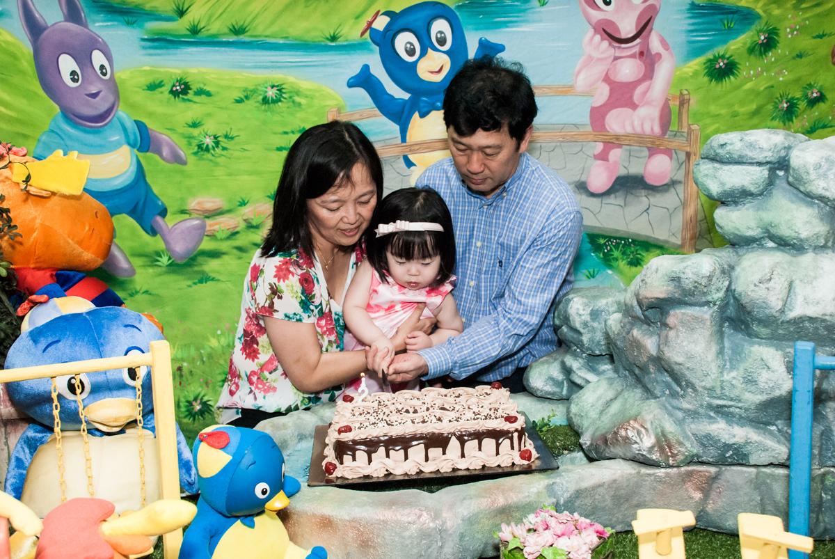 cortando o primeiro pedaço de bolo no fotografia da família na mesa temática no Buffet Viva Vida, Butantã, São Paulo, aniversário de Julia Yumi, tema da festa Backardigans