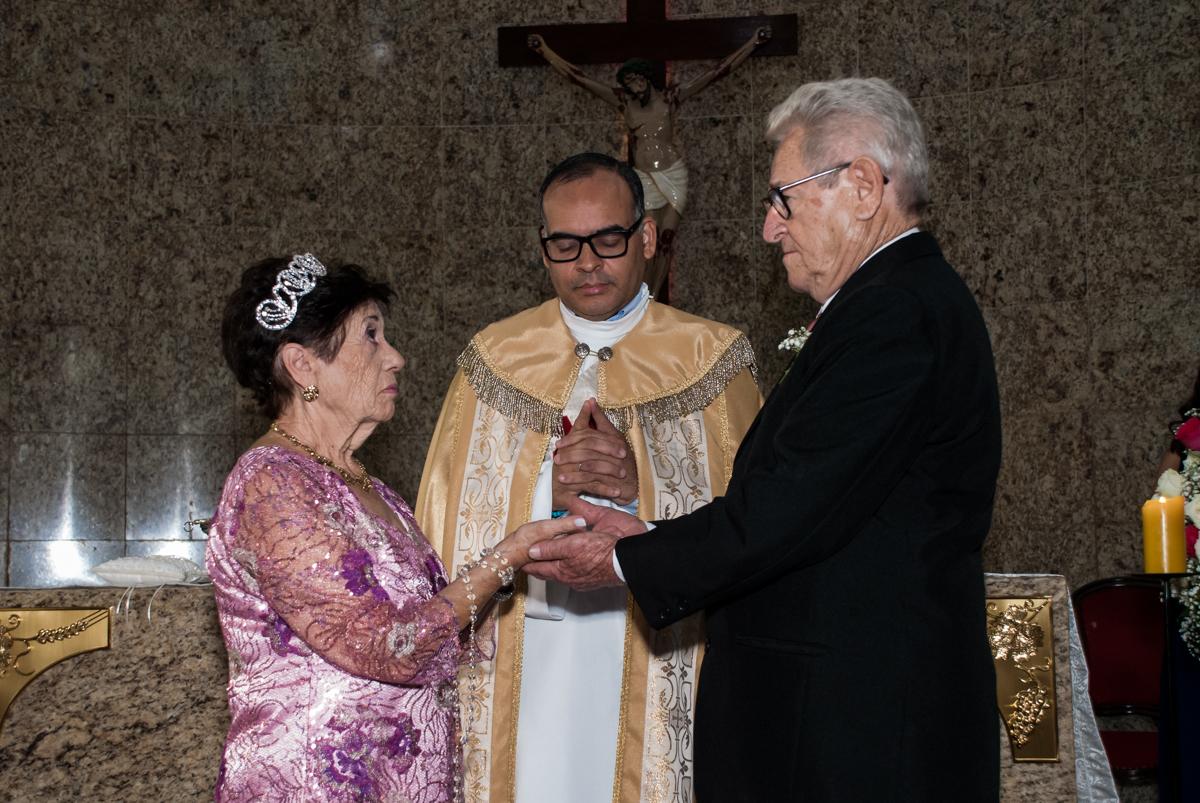 O padre abençoa as alianças na Bodas de Ouro Maria Luiza e José Rodrigues, igreja Santa Ângela e São Serapio, Ipiranga