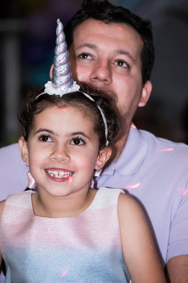 feliz vendo a retrospectiva no Buffet Planeta Kids, Lapa, São Paulo, aniversario de Sarah 8 anos, tema da festa Unicórnio