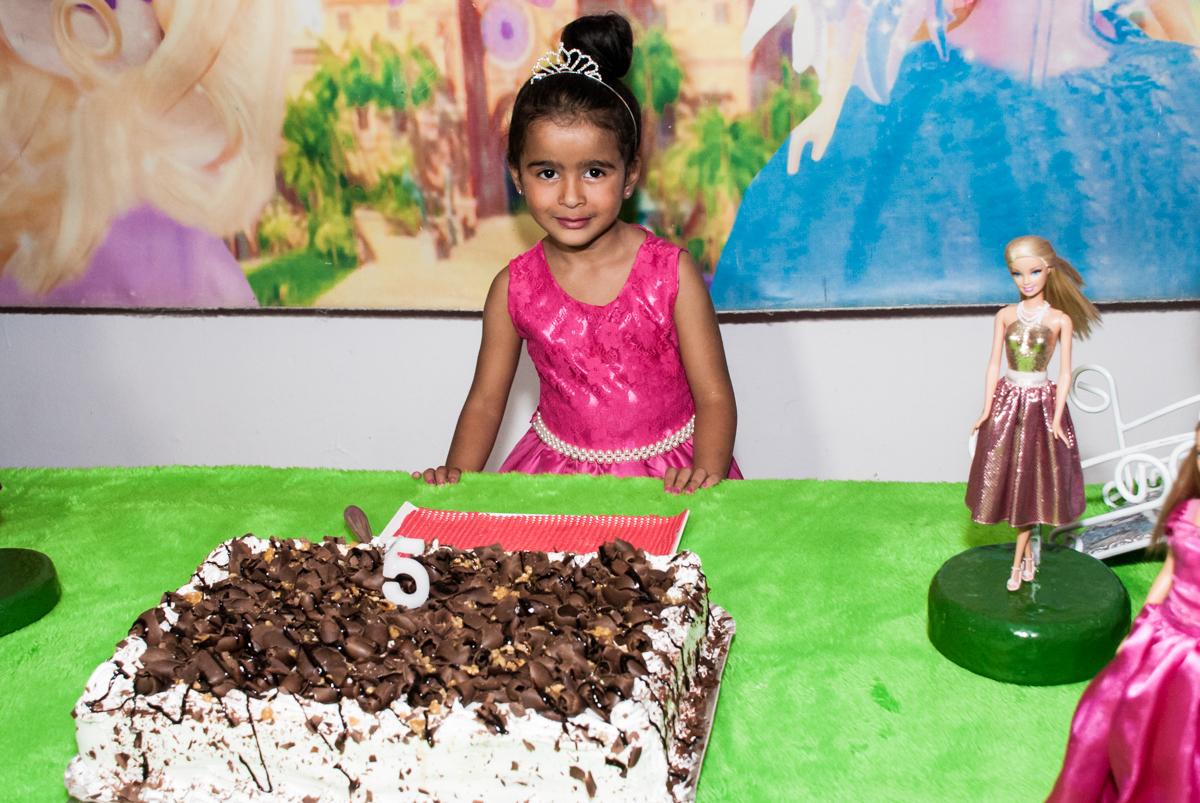 posando para a foto ao lado do bolo