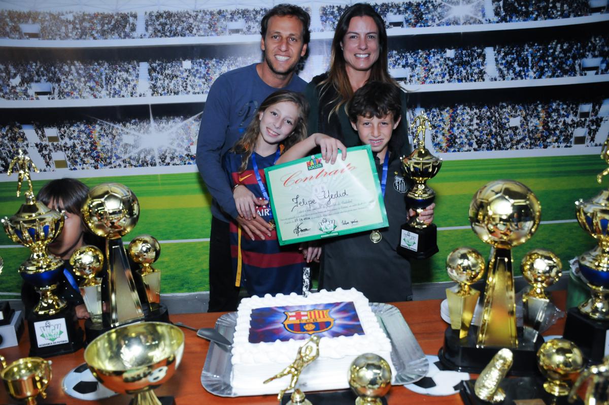 Fotografia do aniversariante e família com o contrato do jogador no Buffet High Soccer