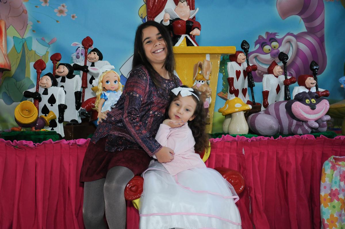 Foto da aniversariante e irmã na mesa Alice no País das Maravilhas no Buffet Magic Joy