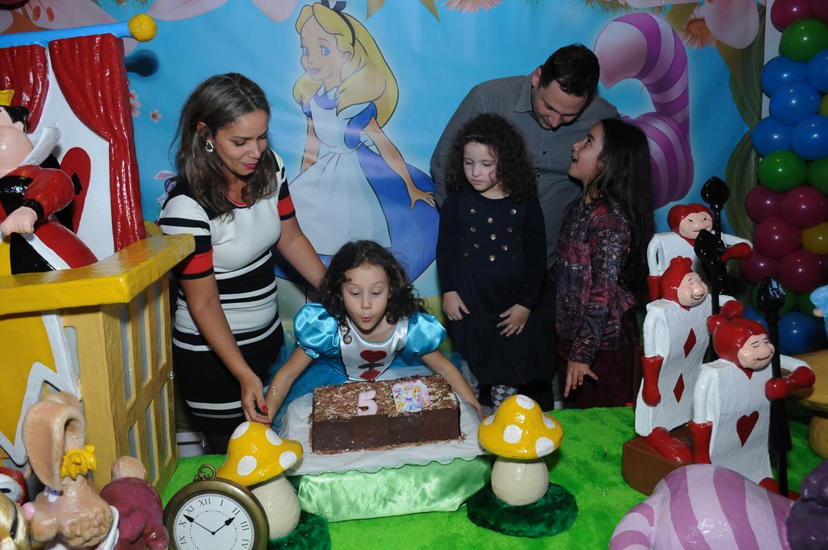 Fotografia da aniversariante soprando a velinha do bolo no Buffet Magic Joy