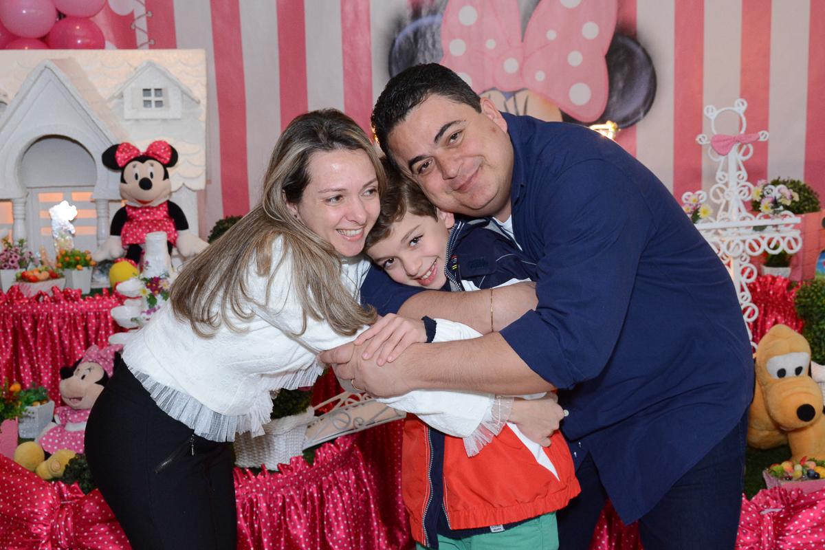 Pais abraçando o irmãozinho de Lorena em frente a mesa decorada  no Buffet Planeta Kids, São Paulo - SP