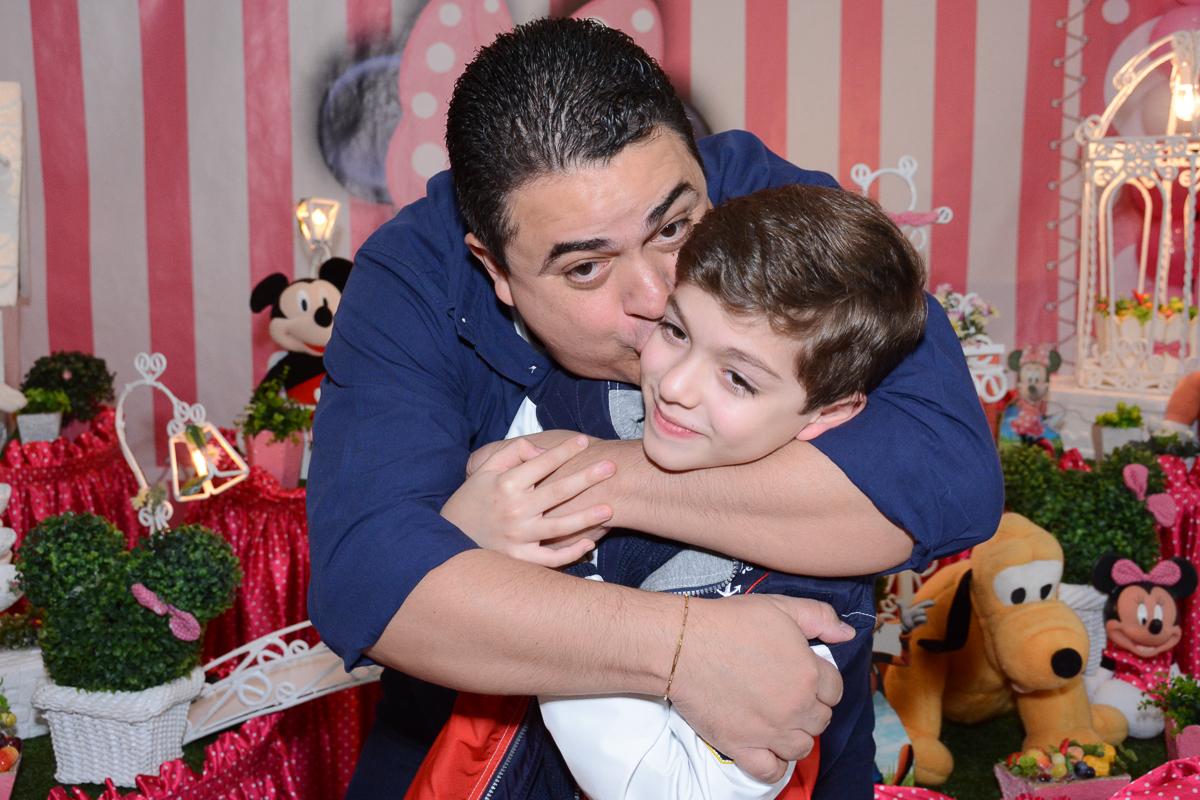 Papai beijando o irmãozinho de Lorena  em frente a mesa decorada  no Buffet Planeta Kids, São Paulo - SP