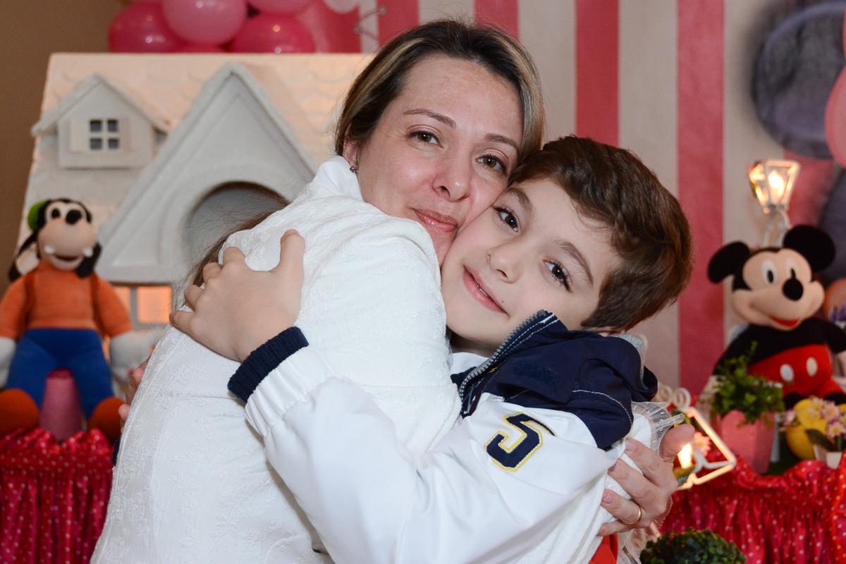 Mamãe de rostinho colado com o irmãozinho da Lorena em frente a mesa decorada  no Buffet Planeta Kids, São Paulo - SP