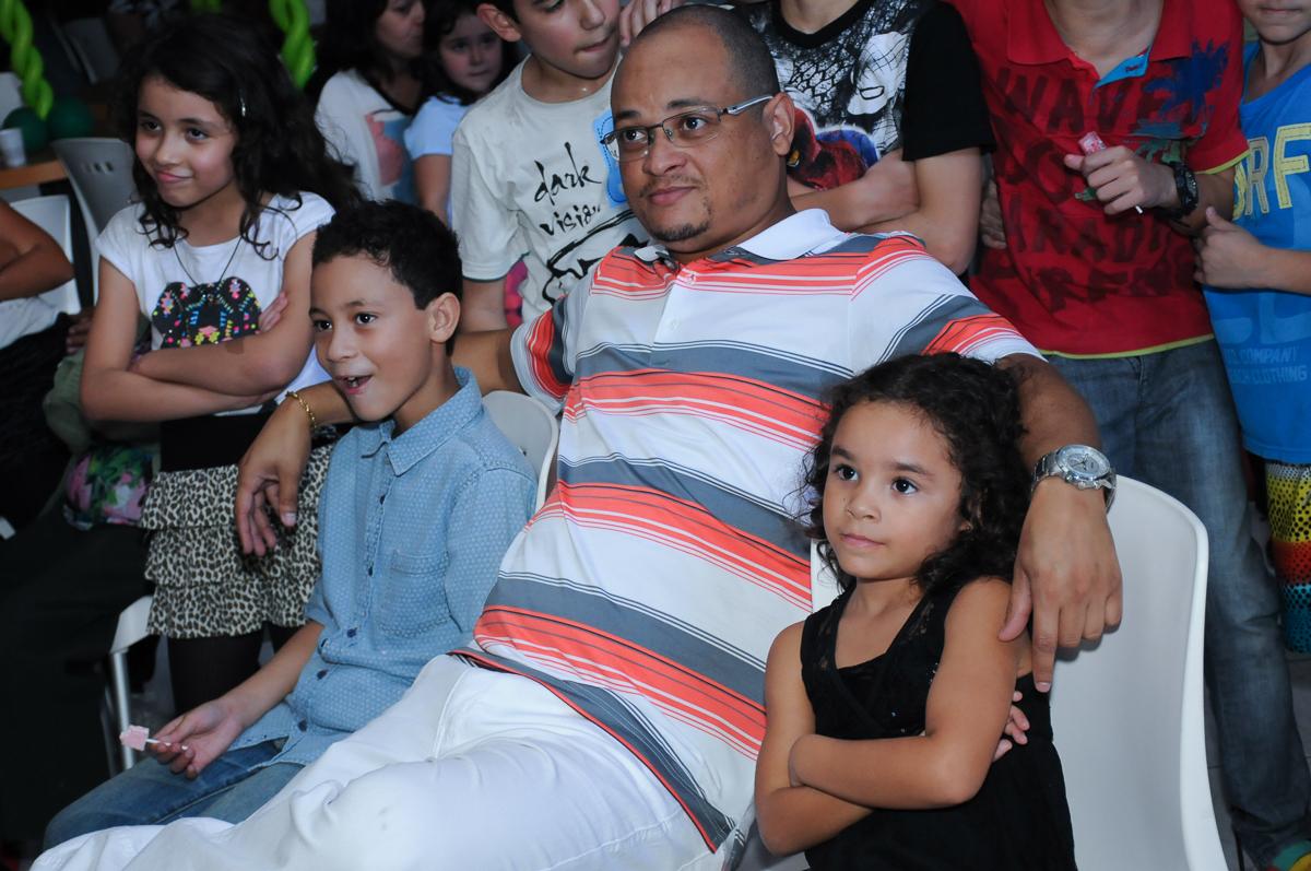 Gabriel, Anna e o papai assistindo a retrospectiva  Buffet Zureta-Osasco -SP