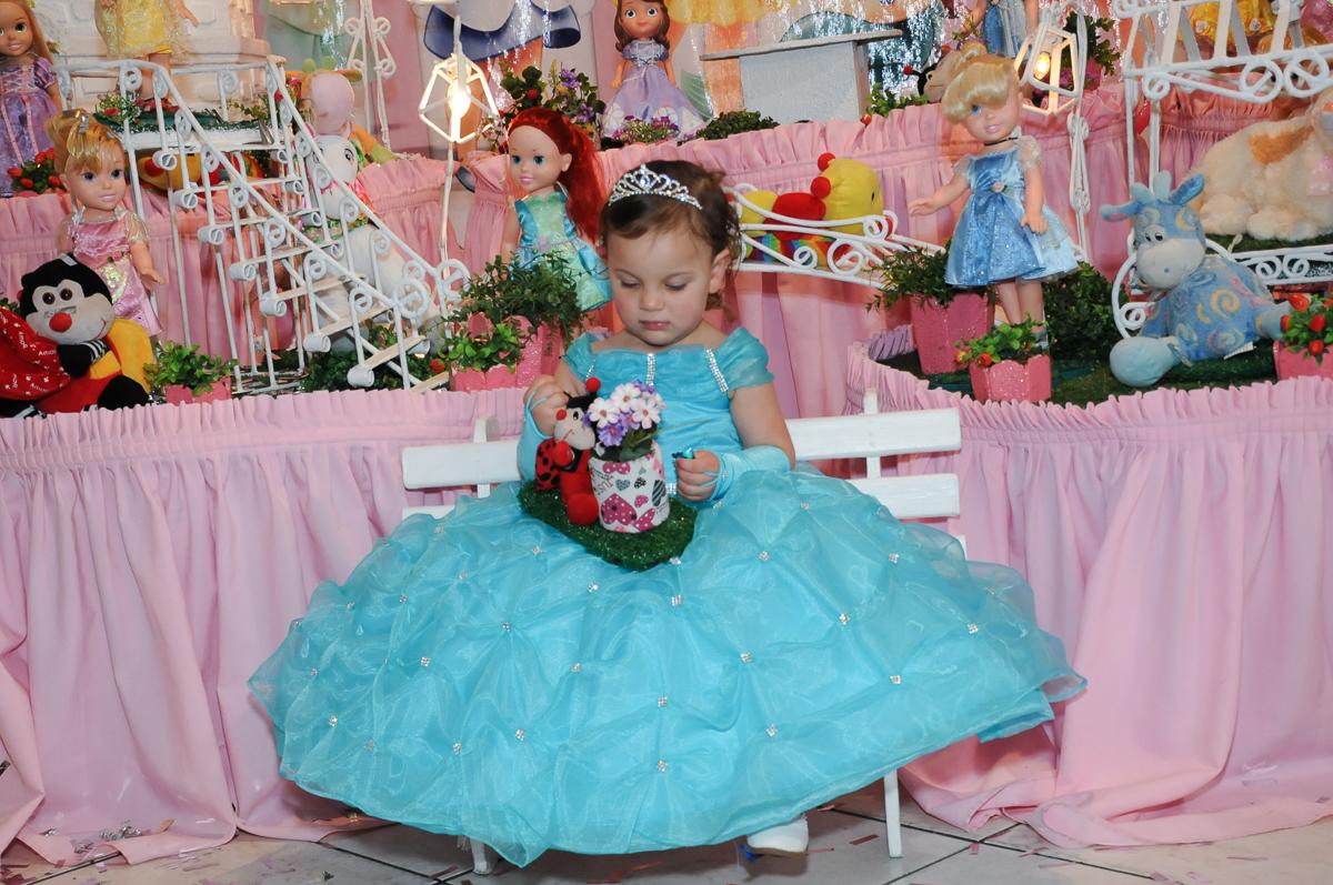 valentina sentada no banquinho em frente a mesa do parabéns no Buffet Fábrica da Alegria, Osasco