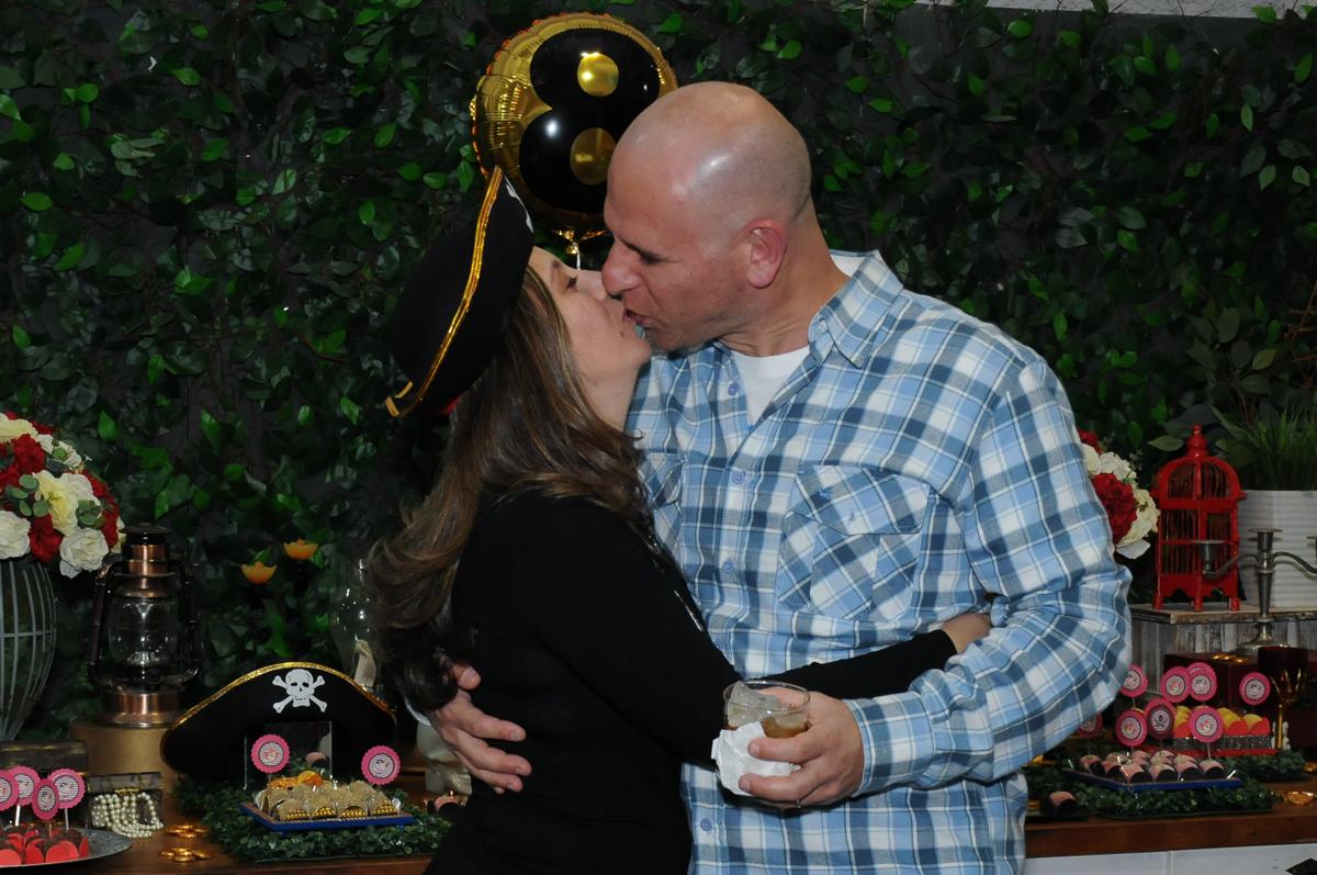 beijo dos pais em frente a mesa piratas do caribe no Buffet Espaço Vila da Arte