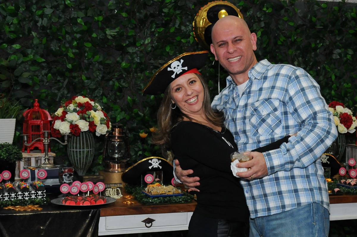 foto dos pais da giulia felizes em frente a mesa piratas do caribe no Buffet Espaço Vila da Arte