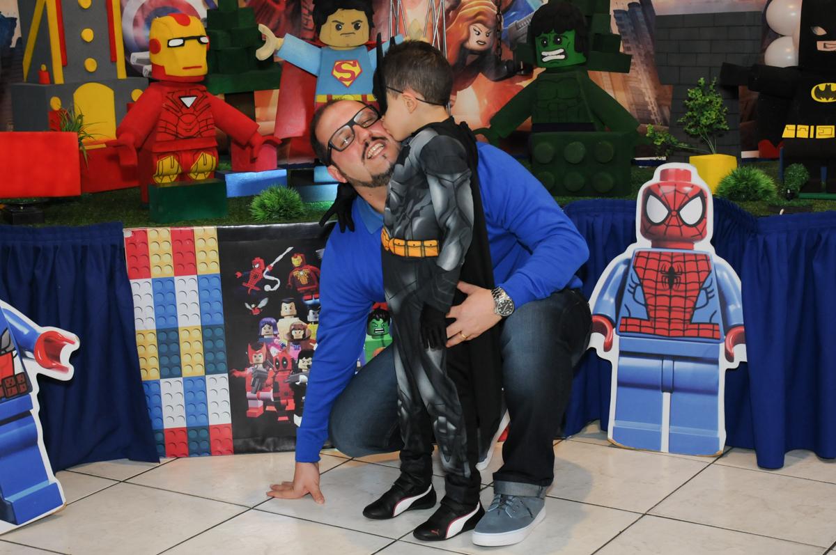 matheus dando beijinho no papai em frente a mesa decorada lego no buffet fábrica da alegria, osasco