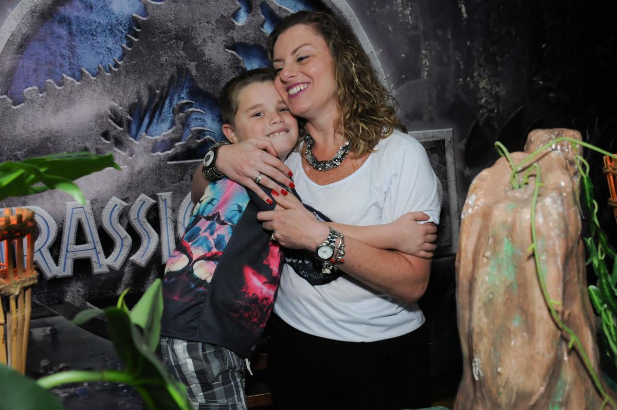 abraço carinhoso da mamãe em frente a mesa decorada dinossauros no buffet espaço boo, Lapa, São Paulo