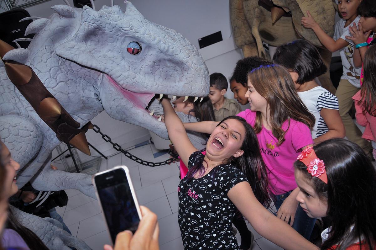 colocando a mão na boca do dinossauro rex no Buffet infantil Max Mania, Panambi