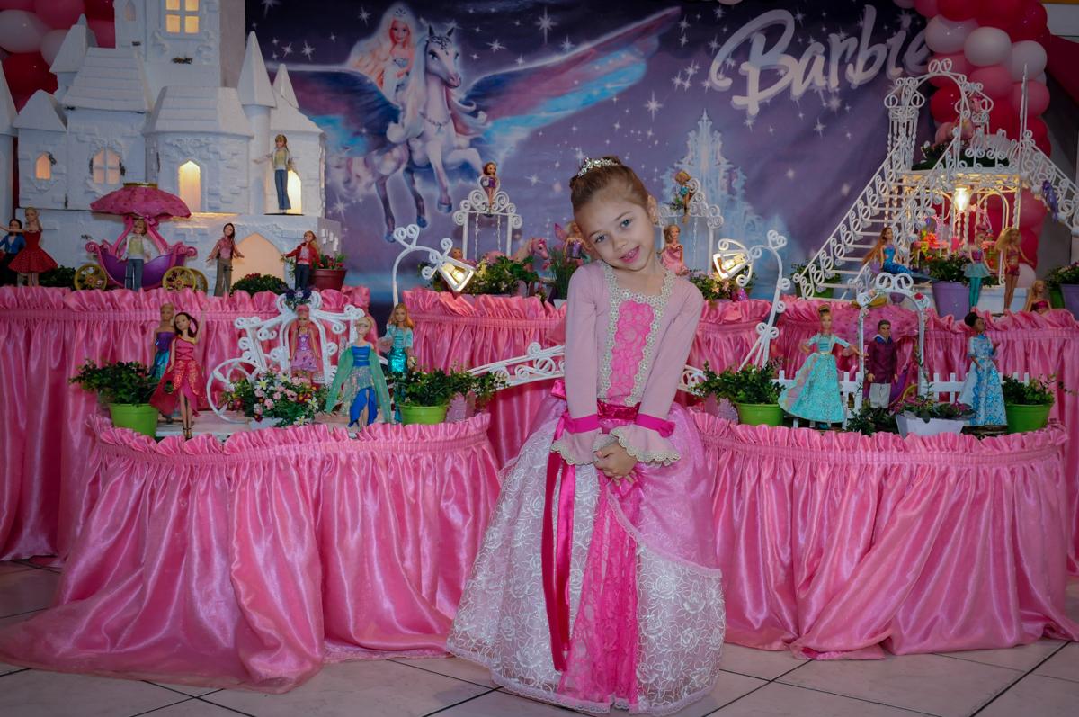 sophia em frente a mesa decorada da barbie no Buffet Fábrica da Alegria, Unidade Osasco