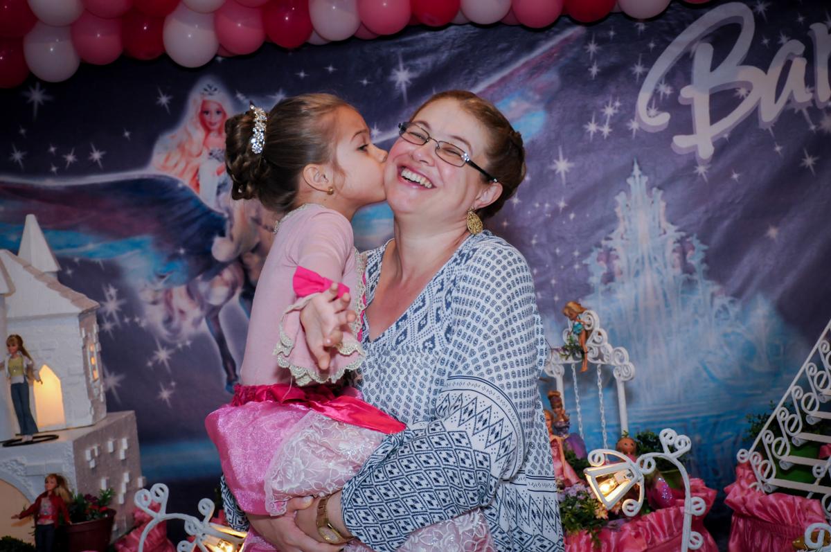 beijo da aniversariante em sua mãe em frente a mesa decorada barbie no Buffet Fábrica da Alegria, Unidade Osasco